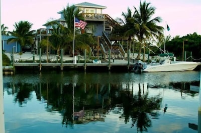 View of the house & its 100 ft dock while approaching by boat from the canal.