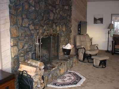 Corner of the living room with stone-faced/WOOD-burning fireplace.