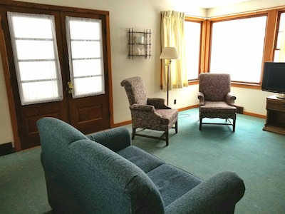 Comfy living room with door to screened-in front porch.