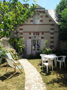 Un coin de campagne en centre ville: un cottage et un jardin fleuri de roses