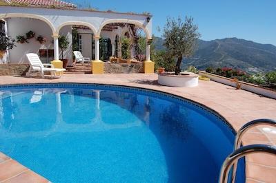 Blick über Pool, Terasse, Blumen und Berge