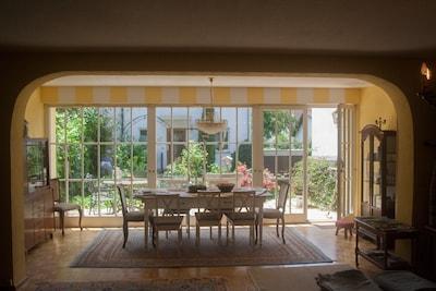 Das sehr geräumige Wohnzimmer mit großem Esstisch, Terrasse und Garten