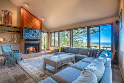 Living room with fireplace, breathtaking views & 65-inch smart television.