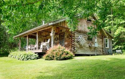 Exterior of log cabin in summer.