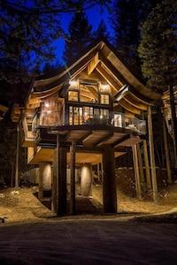 Tamarack treehouse Chalet, lit up on an autumn evening