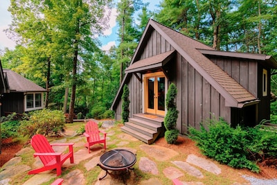Exterior of the carriage house with firepit and 4 adirondack chairs for enjoying the large, wooded back yard.