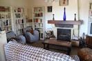 Salon avec canapé lit, deux fauteuils, bibliothèque, cheminée