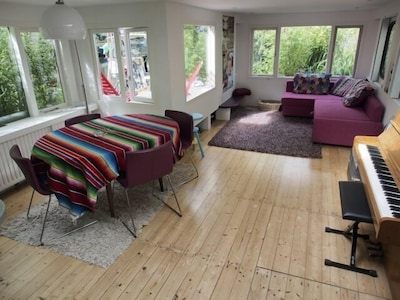 Living room with sofa bed, piano and dining table.