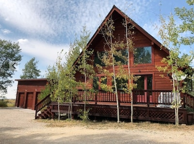Cabin with two bedrooms and two bathrooms, deck in the trees on the back.