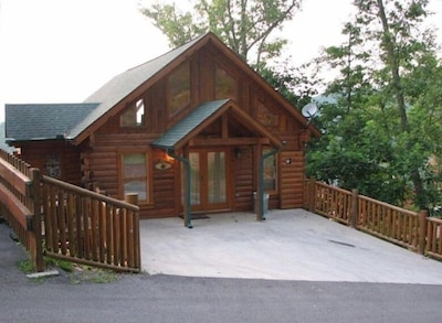 Cabin front with double entry doors and two parking spaces for cars