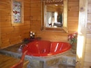Red heart jacuzzi tub with stone surround and stained glass window accent