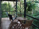 Private porch surrounded by jungle, looking down on the ocean below.