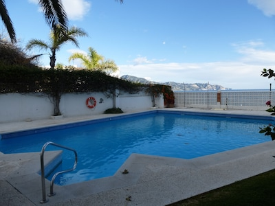 Swimming pool with grassy area.  The beach is just below.