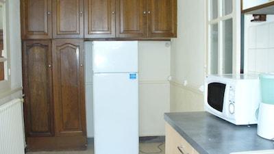 cuisine indépendante juxtant la salle à manger avec refrigrérateur-congélateur.
