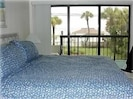 Master bedroom with great view of pool and beach