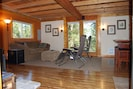Open living/dining area with queen sleeper sofa and french doors to large deck