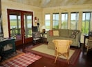 Den area with wood stove overlooking Huggins Island and surrounding waters.