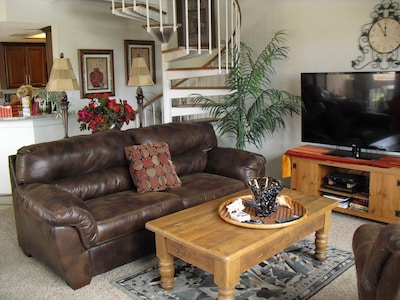 Living Room with leather queen sleeper, 55' big screen TV and spirals to master
