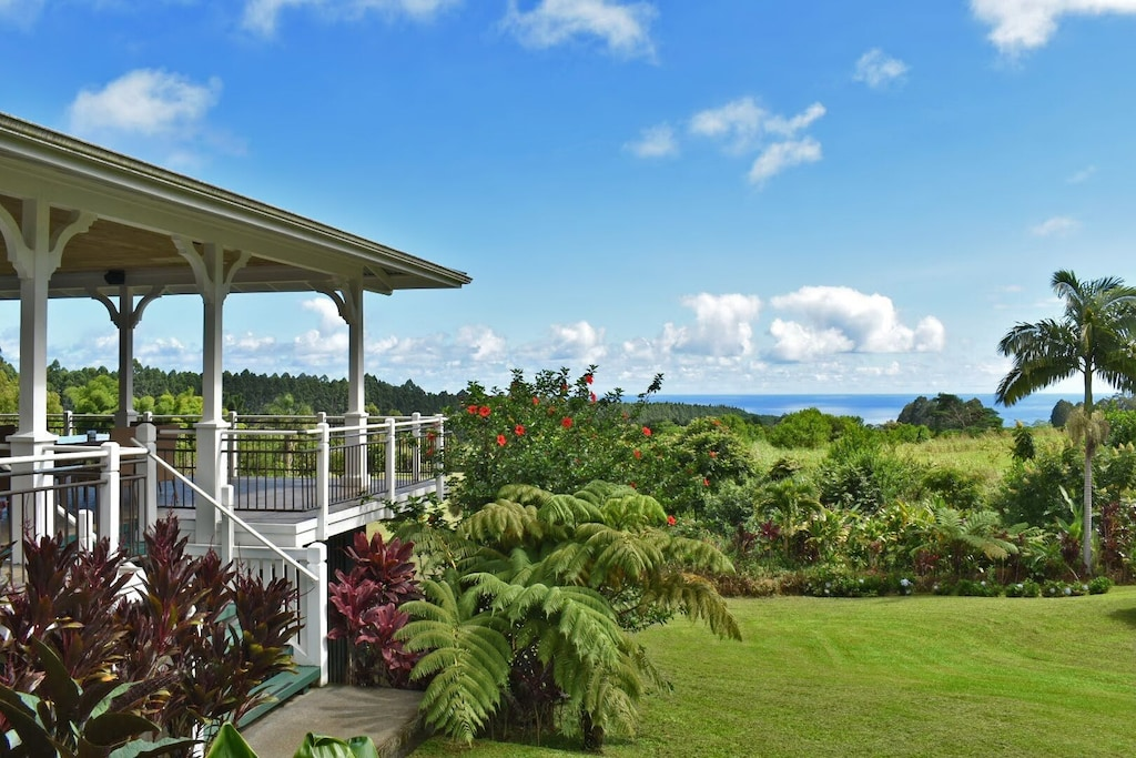 Porch and house in a lush garden with ocean views