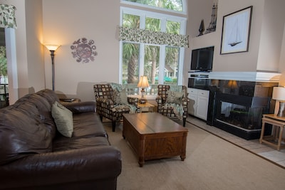 Comfortable sitting arrangement around lovely fireplace and large screen TV.