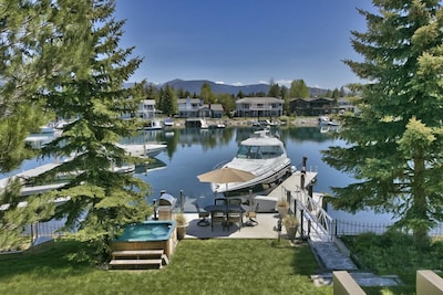 View from upper deck over the yard, hot tub, overwater deck, water dock and boat
