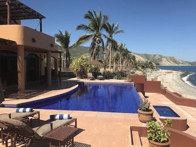 View of backyard patio w/ sunning chairs, infinity edge pool & large Jacuzzi.