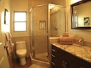Bathroom featuring granite counters, custom shower, fully stocked w amenities.