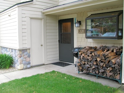 The entry features perennial flowers and free firewood included in rental fee.
