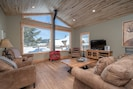 """Bright, sunny living room with views of the mountains, a gas stove and a 55"""" TV."""