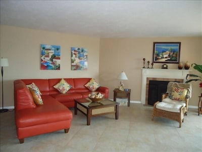 """Living room w/ wood burning fireplace, 52"""" TV, opens to balcony and dining area."""