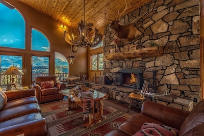 Great Room with wood ceiling, log accents, slate floors, and Pikes Peak view.