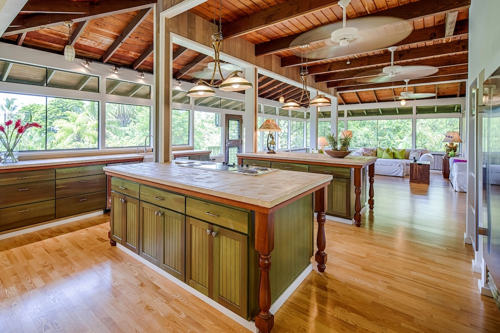 Kitchen in a wooden interior with open windows overlooking lush foliage