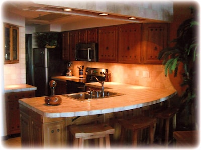 Kitchen w/ breakfast bar, marble countertops, wine niche...