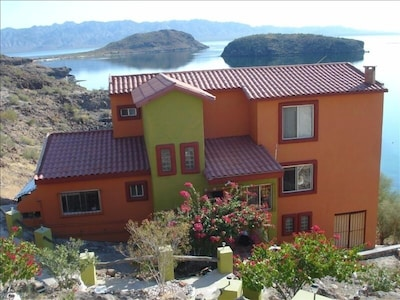 A view from our parking area shows the villa with new colors, and the bay.