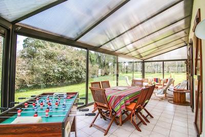 La grande véranda, bien orientée : un lien apprécié entre maison et jardin clos.