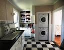 Kitchen with washer-dryer, sink, cupboards and refrigerator