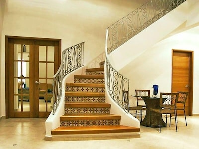 Living room staircase to 2nd floor, king suite, & private solarium