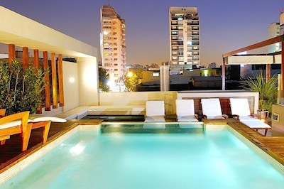 Rooftop luxury - pool, shower and lounge seating with a view of Buenos Aires!