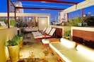 Relaxing outdoor lounge with pool, firepit, rainshower and views of the city