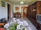 Salon avec vue vers l'entrée et le couloir vers les chambres et le bain.