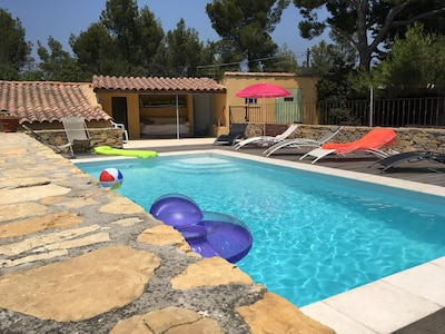 la piscine 7X4 avec à l'arrière son coin à l'ombre, douche et canapé