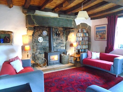 The Longhouse lounge has 3 comfortable sofas and a wood-burning stove