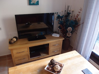 Lounge with oak furniture and large flat TV