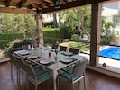 Rear terrace and dining table overlooking pool