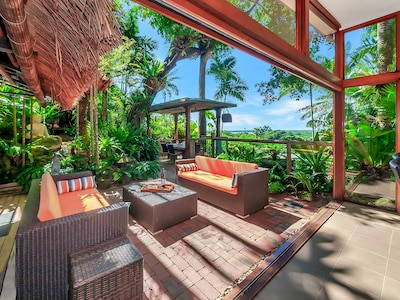 Tropical outdoor entertaining and dining areas looking  out over the water.