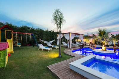 Lawn covered garden and wooden deck around the pool.