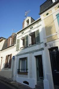La façade de la maison et ses volets verts