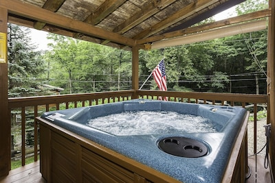 large hot tub on covered deck.
