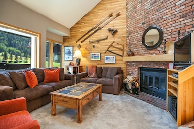 Great room with vaulted ceilings and views of river, lake and mountains beyond.