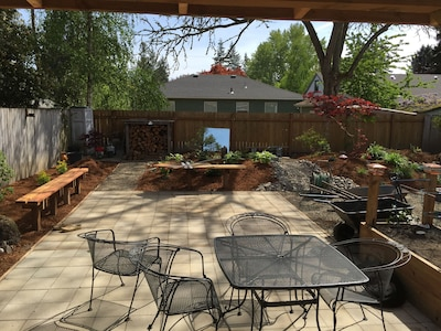 Back yard with built in benches, garden, table and chairs, firewood and fire pit